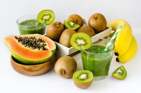 papaya: Green healthy kiwi tropical fruits smoothie with papaya and bananas Stock Photo