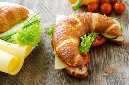 healthy snack: Croissant sandwich with cheese and vegetables for healthy snack, rustic wooden background