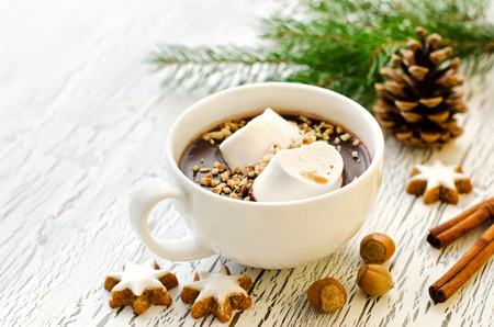 Hot winter beverage with nuts on white wooden background
