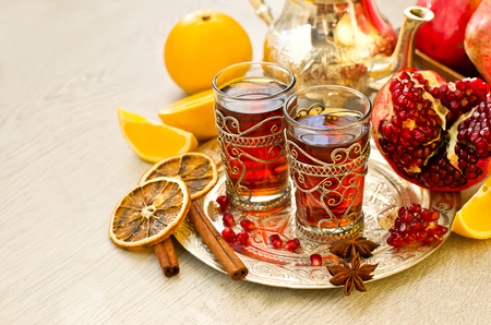Tea with spices and pomegranate on a tray selective focus copy space