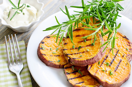Cut sweet potato baked with rosemary on the plate
