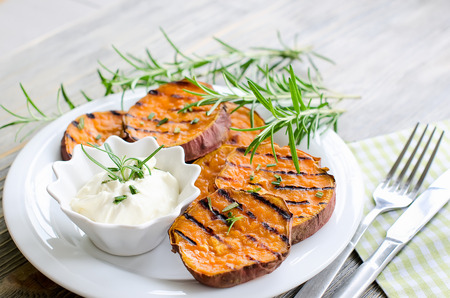 Cut sweet potato baked with rosemary on the plate for dinner Standard-Bild