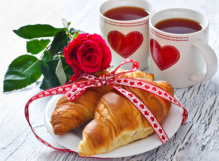 desayuno romantico: Romantic breakfast with tea in cups, croissants and rose