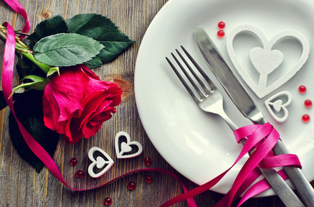 Romantic dinner with rose, tableware and hearts on wooden background