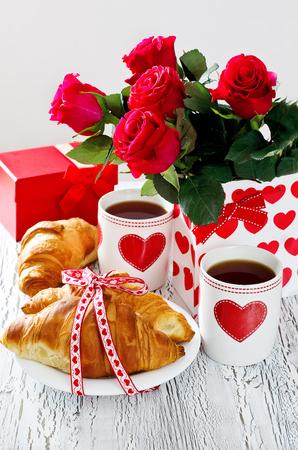 desayuno romantico: Desayuno romántico con té en tazas, croissants, las rosas y caja de regalo Foto de archivo
