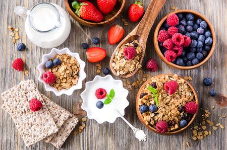 comiendo frutas: Desayuno con muesli, bayas, pan crujiente y el yogur