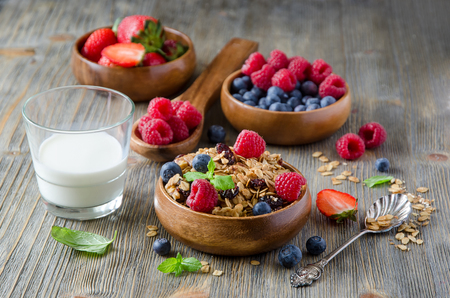Breakfast with rolled oats and berries in wooden bowls