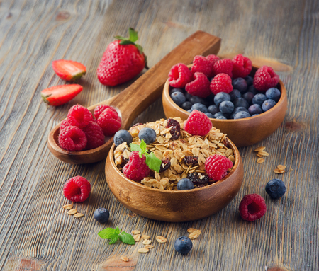 Healthy reakfast with rolled oats and berries in wooden bowls, rustic background, square image Archivio Fotografico