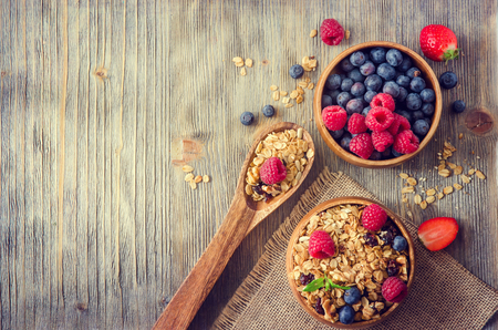 Breakfast with fresh berries, granola or muesli on rustic wooden background, health and diet concept, copy space