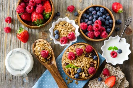 yogur: Saludable desayuno, muesli, frambuesas, ar�ndanos, fresas, pan crujiente y el yogur, la salud y el concepto de dieta Foto de archivo