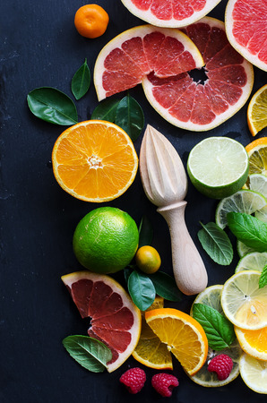 Slices of grapefruit, orange, lime with mint and wooden squeezer