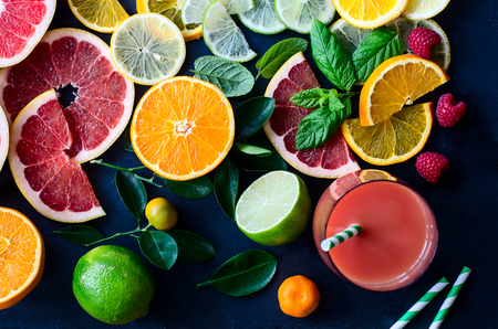 Citrus juice and slices of orange, grapefruit, lemon. Vitamin C. Black background Imagens