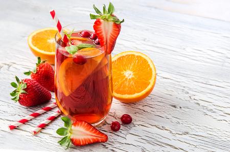 vaso de jugo: Sangría con naranjas y fresas espacio de copia fondo blanco