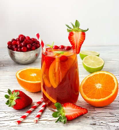 coctel de frutas: Sangria with oranges and strawberries in glasses white background