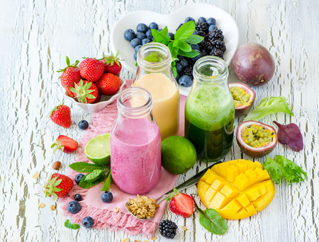summer diet: Berry and fruit smoothie in bottles, healthy summer detox yogurt drink, diet or vegan food concept, fresh vitamins, mango, lime, passtion fruits Stock Photo