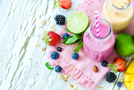 Berry and fruit smoothie in bottles, healthy summer detox yogurt drink, diet or vegan food concept, fresh vitamins, mango, lime Archivio Fotografico