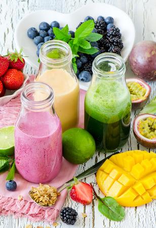 Berry and fruit smoothie in bottles, healthy summer detox yogurt drink, diet or vegan food concept, fresh vitamins, mango, lime, passtion fruits Stockfoto