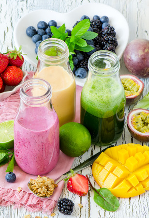Berry and fruit smoothie in bottles, healthy summer detox yogurt drink, diet or vegan food concept, fresh vitamins, mango, lime, passtion fruits Archivio Fotografico