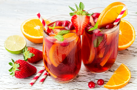 summer fruits: Cranberry drink, homemade lemonade or sangria with citrus fruits and berries on white background, refreshing cocktail for hot summer days Stock Photo