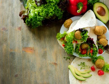 wraps: Tortilla wrap with falafel, avocado and fresh salad, vegetarian healthy food, vegan concept copy space Foto de archivo