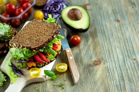 新鮮な食材とビーガン ライ麦サンドイッチ: アボカド、サラダ、トマト、ニンジンは、健康的な食事、ビタミンやダイエット食品のコピー スペース 写真素材