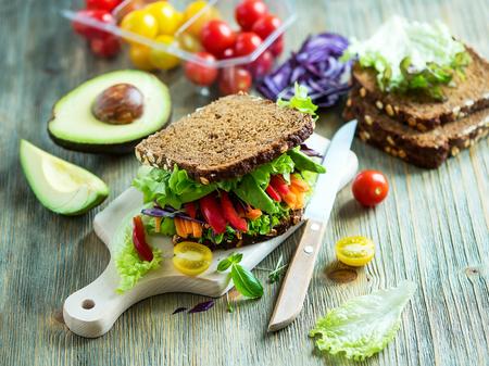 Vegan rogge sandwich met verse ingrediënten: avocado, sla, tomaten, wortelen, voor een gezonde maaltijd, vitamine en dieetvoeding