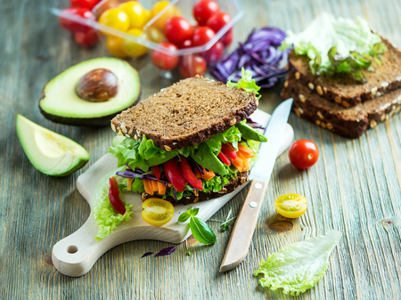 Vegan rye sandwich with fresh ingredients: avocado, salad, tomato, carrots, for healthy meal, vitamin and diet food