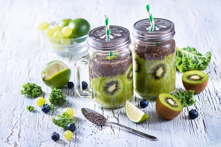 Green fresh detox vegan superfoods smoothie, vitamins diet drink with kale, chia seeds, lime, kiwi, blueberries. Stock Photo