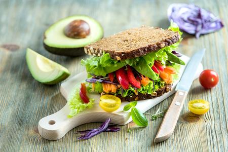 botanas: Emparedado de centeno vegano con aguacate fresco, ensalada, verduras, bocadillo saludable, comida de vitaminas y dietas