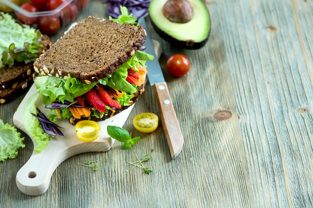 dieta sana: Vegan rye sandwich with fresh avocado, salad,veggies, healthy snack, vitamin and diet food