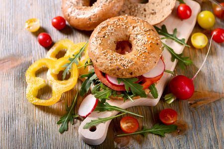 picknick: Vegetarian bagel sandwich with fresh veggies and arugula salad, vegan healthy food, lunch, breakfast, picknick snack