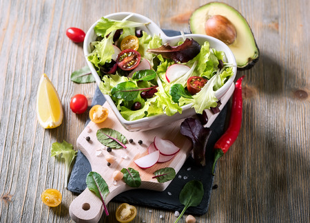 Healthy green salad with avocado, mangold leaves, red beans and cherry tomatoes. Vegan snack, vitamins, vegetarian food and diet concept