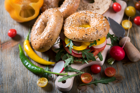 picknick: Vegetarian bagel sandwich with fresh veggies and arugula, vegan healthy food, lunch, breakfast, picknick snack Stock Photo