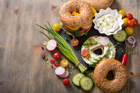 picknick: Vegetarian bagel sandwich with cream cheese, fresh veggies and arugula, healthy food, lunch, breakfast, snack
