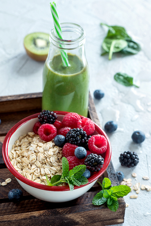 Healthy breakfast, muesli with berries and green smoothie bottle, vegan, diet and detox concept, clean eating, vitamin food, healthy lifestyle