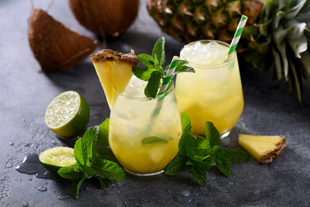 Cold pineapple cocktail with crushed ice, lime, coconut and mint, tropical refreshing lemonade drink Stockfoto