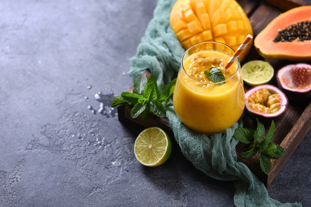 Healthy smoothie with tropical fruits, pineapple, papaya and passion fruit, exotic vitamin drink Stock Photo