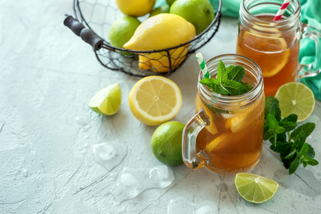 Iced tea, summer cold drink  with lemon, lime and mint, ice cubes, refreshment