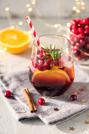 Winter cocktail with cranberries and orange, festive cold drink, punsh for christmas