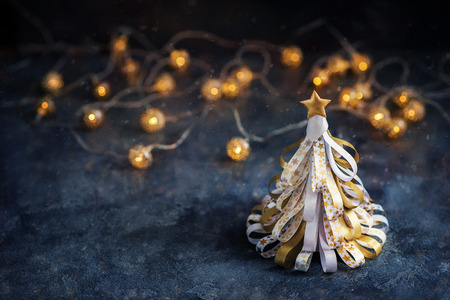 Decorative golden christmas tree with lights and sparkles, festive copy space background Stock Photo