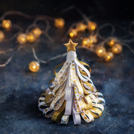 Decorative golden christmas tree with lights and sparkles, festive square image