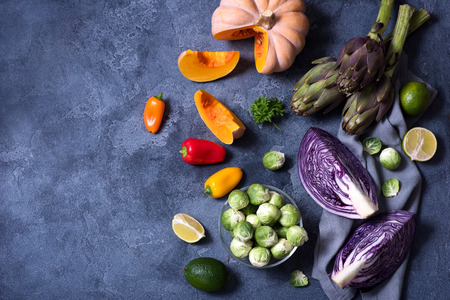 Healthy vegan cooking ingredients, fresh vegetables, clean eating concept, copy space background, flat lay. red cabbage, artichokes, brussel sprouts, pumpkin, top view Archivio Fotografico