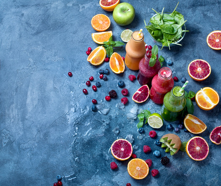 Colorful detox smoothie in bottles, with spinach, berries, mango, kiwi, lime. Summer diet fresh vegan drink for breakfast or snack, copy space background Imagens