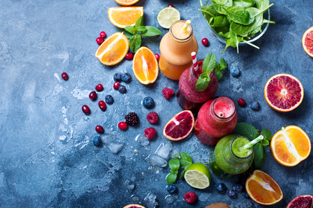 Colorful detox smoothie in bottles, summer diet fresh drink, red, green, yellow smoothie with berries and fruits Imagens