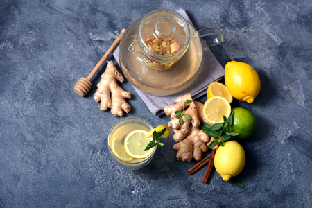 Healthy ginger tea with mint, hot vitamin drink with lemons, top view,copy space background Imagens