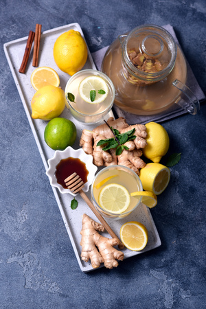 Healthy ginger tea, hot vitamin drink with lemons, vertical image
