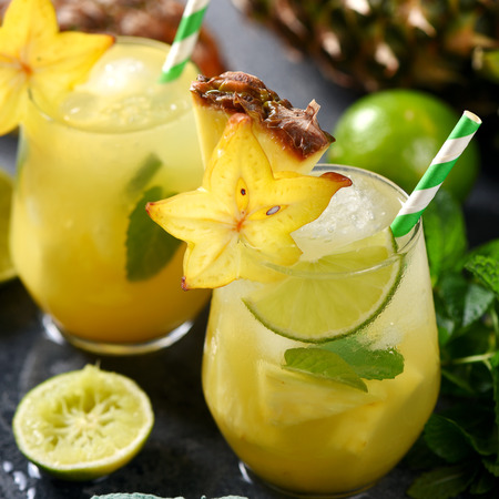 Cold tropical cocktail with crushed ice, carambola, pineapple, square image