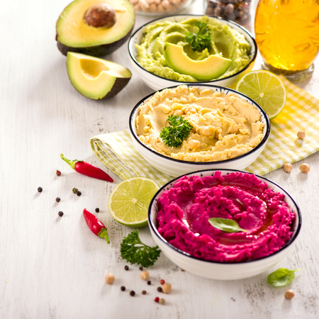 Colorful hummus, different dips, vegan snack, beetroot and avocado hummus, vegetarian eating, square image