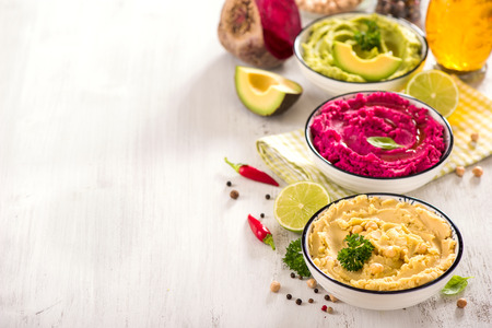 Colorful hummus, different dips, vegan snack, beetroot and avocado hummus, vegetarian eating, copy space background
