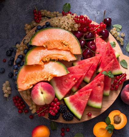 Fresh summer fruits and berries on a round cutting board, watermelon, cantaloupe, cherries, vegan raw eating, diet vitamins concept